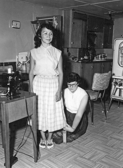 """Mary Anne Crocker measures the hem of a skirt for a young homemaker on the Warm Springs Indian Reservation"""""""