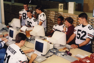 Football players using library computers