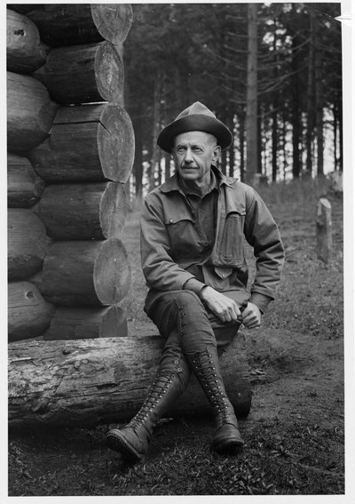 Black and white photograph of George Wilcox Peavy sitting on a log.