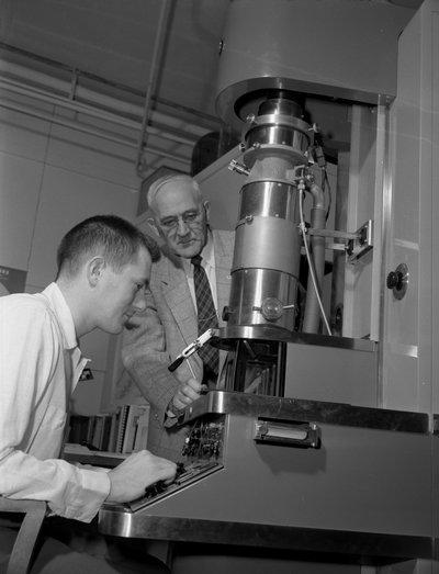 Black and white photograph of Francois Archibald Gilfillan examining an electron microscope.