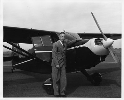 Black and white photograph of August LeRoy Strand with a Voyager 150 plane.
